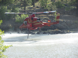 Helicopters dip in Santa Fe dam for water to fight the fire.